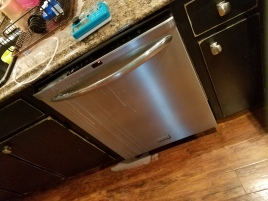 Kitchen counter and dishwasher with milk spilling down onto the floor