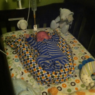 Newborn baby on elevated mattress with feeding tube